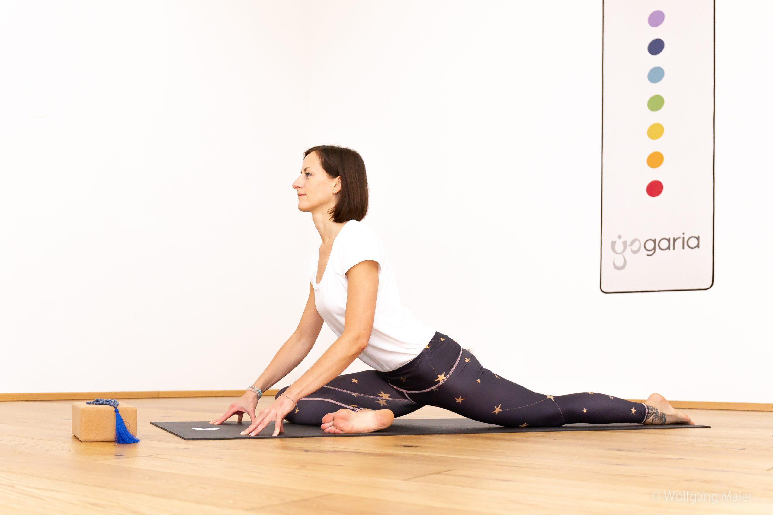 Klaudia, die Eigentümerin der Yogaria in der Position der Taube, man sieht sie von der Seite im großen Yogaraum, vor ihr steht ein Block mit einem Yogamala und im Hintergrund sieht man ein Wandbild mit dem Logo der Yogaria und den 7 Punkten der 7 Chakrafarben