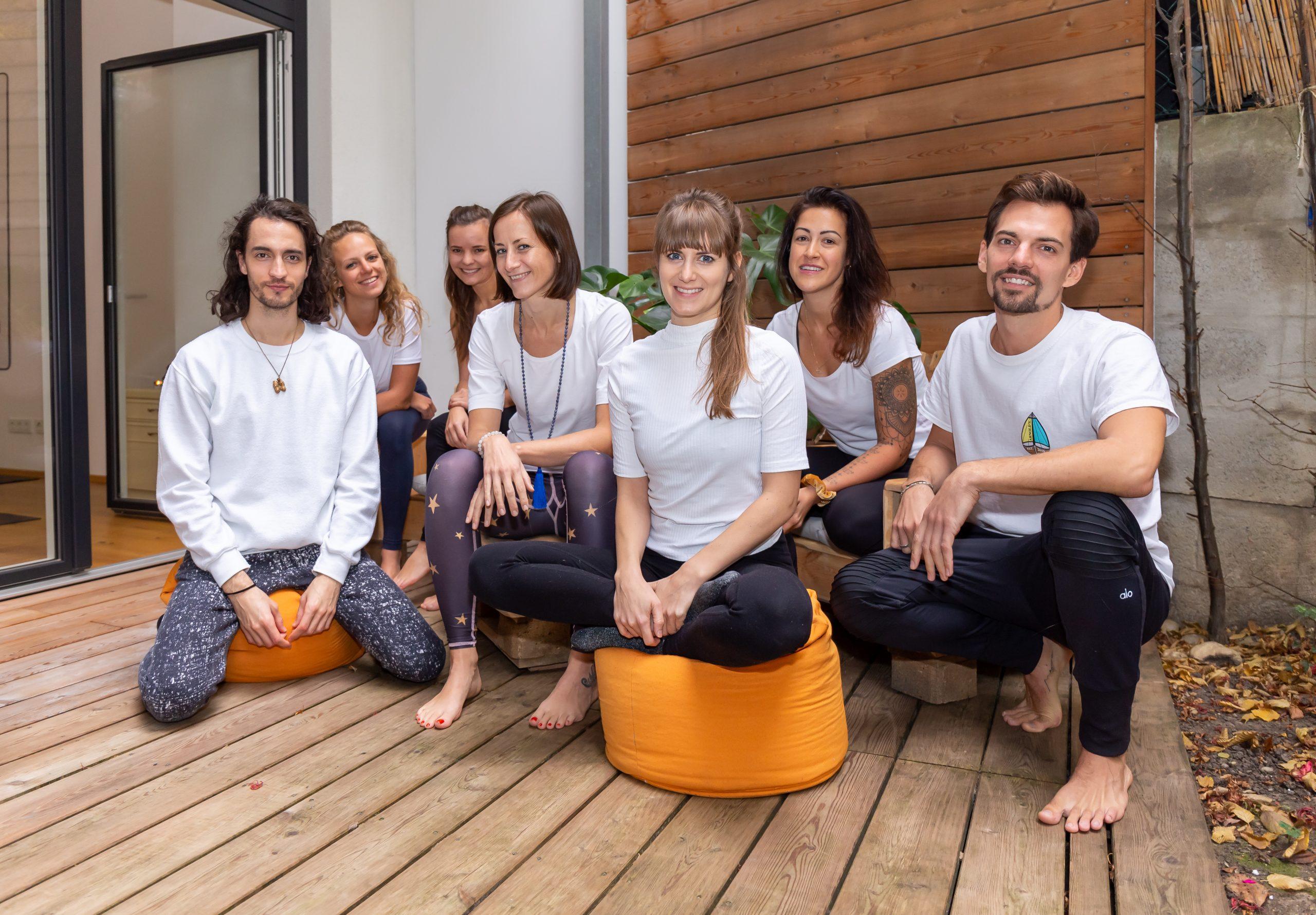 Das Team der Yogaria sitzt auf Sitzkissen auf der Terrasse im Yogastudio, alle Blicken Richtung Kamera und lächeln, man sieht insgesamt 7 Personen.
