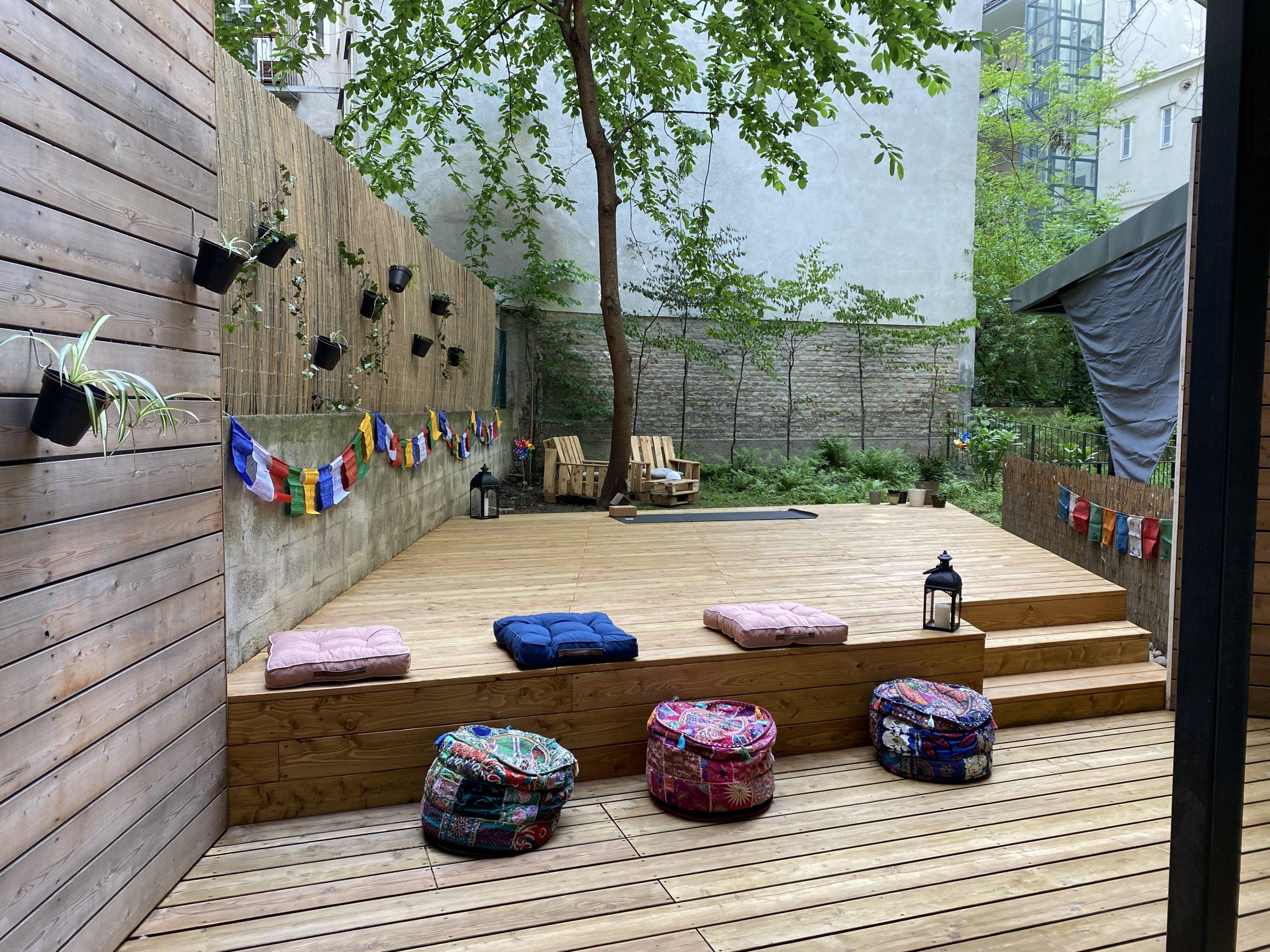 Yogadeck im Garten der Yogaria mit bunten Sitzkissen, 2 Laternen, Nepalfahnen an den Mauern, am Ende des Yogadecks sieht man eine Yogamatte und dahinter noch 2 Gartenmöbel aus Paletten gebaut, ein Blick ins Grüne
