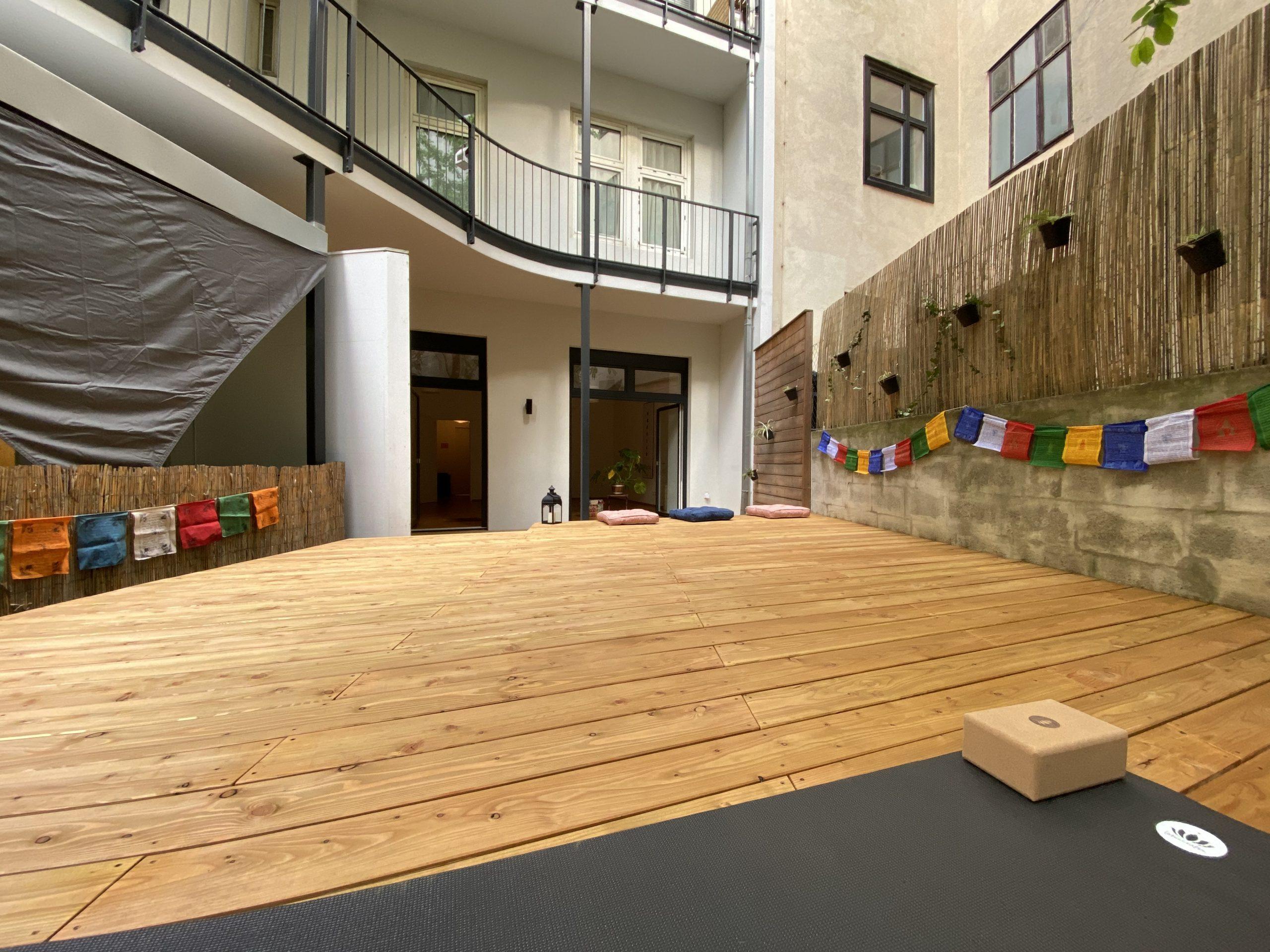 im Vordergrund ein Teil der Yogamatte mit Yogablock, Einstellung der Kamera vom Yogadeck Rictung Gebäude, man sieht das schöne neue Yogadeck, den Eingang über die Terrasse in den Yogaraum und die Dekoration an den Seiten mit den Nepalfähnchen