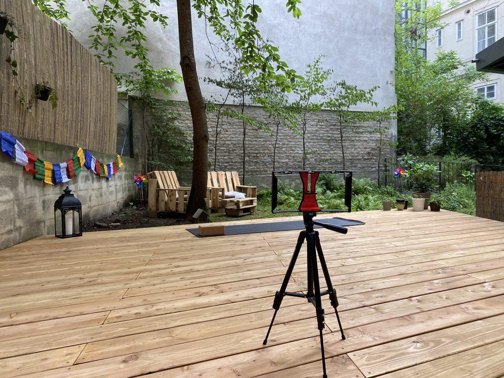 das Stativ der Handyhalterung für die Übertragung der Online Klassen thront in der Mitte des neuen Yogadecks, dahinter sieht man die Yogamatte vor dem grünen Teil des Gartens, eine Laterne und ein paar Nepalfahnen an den Seiten