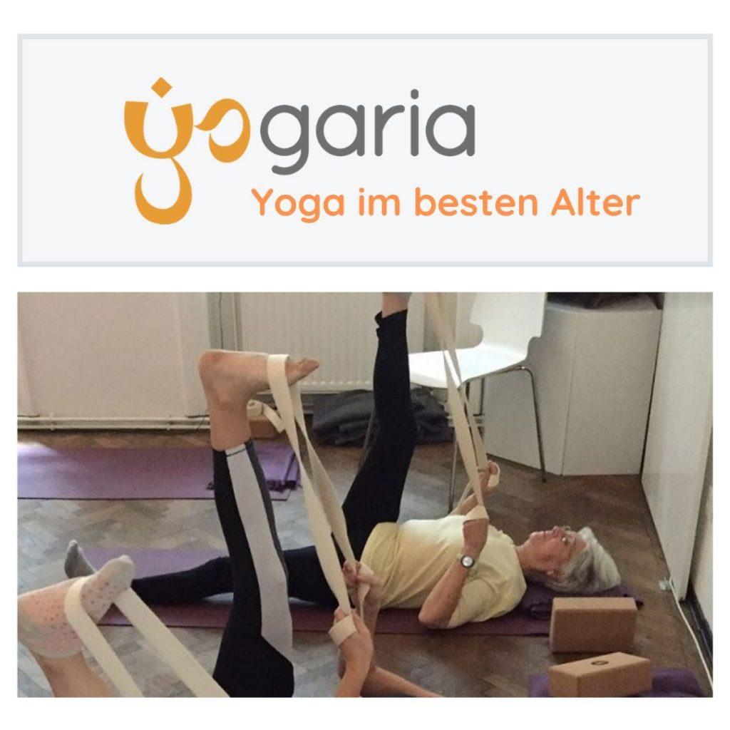 """Titelbild Yoga im besten Alter, man sieht eine """"ältere Dame"""" am Rücken auf einer Yogamatte liegen, sie hält einen Yogagurt mit beiden Händen und zieht ihr rechtes Bein Richtung Oberkörper um die Rückseite ihres rechten Beins zu dehnen"""