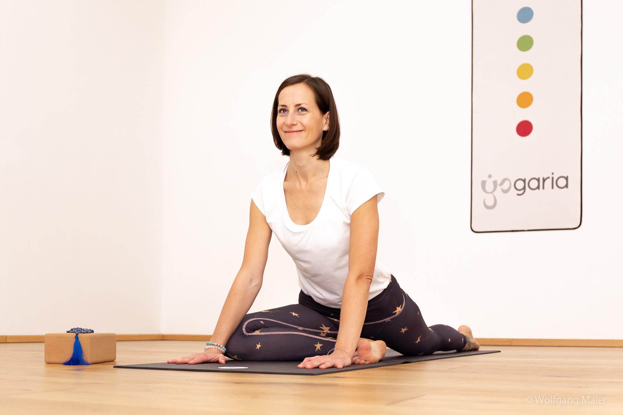 Klaudia in der Yogapose Taube auf der Yogamatte im Yogaraum der Yogaria, dahinter sieht man das Wandbild der Yogaria mit den 7 Chakra-Farben