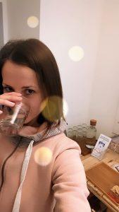 Klaudia trinkt ein Glas gefiltertes Wasser und im Hintergrund sieht man die Informationsbroschüren