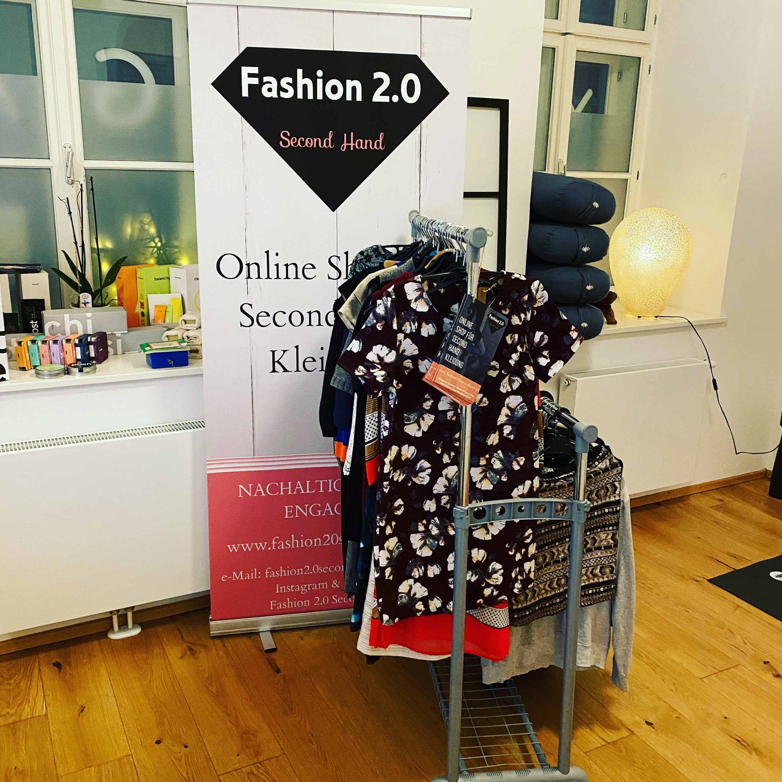 """Ein Kleiderständer mit Kleidern und Oberteilen vor einem Werbebanner auf dem zu lesen ist """"Fashion 2.0"""" auf dem Kleiderständer hängen auch Flyer und alles steht im 2. Yogaraum der Yogaria vor 2 Fenstern"""