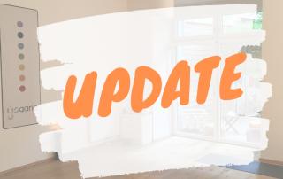 im Hintergrund der große Yogaraum der Yogaria, darüber wie ein dicker weisser Pinselstrich auf dem in orangenen Buchstaben das Wort Update steht