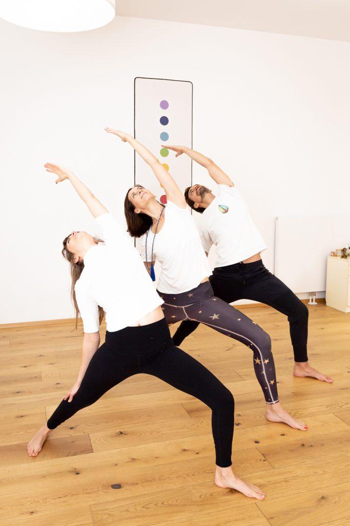 3 Personen in einer Reihe stehend in der Position des Umgekehrten Kriegers, im Raum der Yogaria, eine dynamische Yogapose