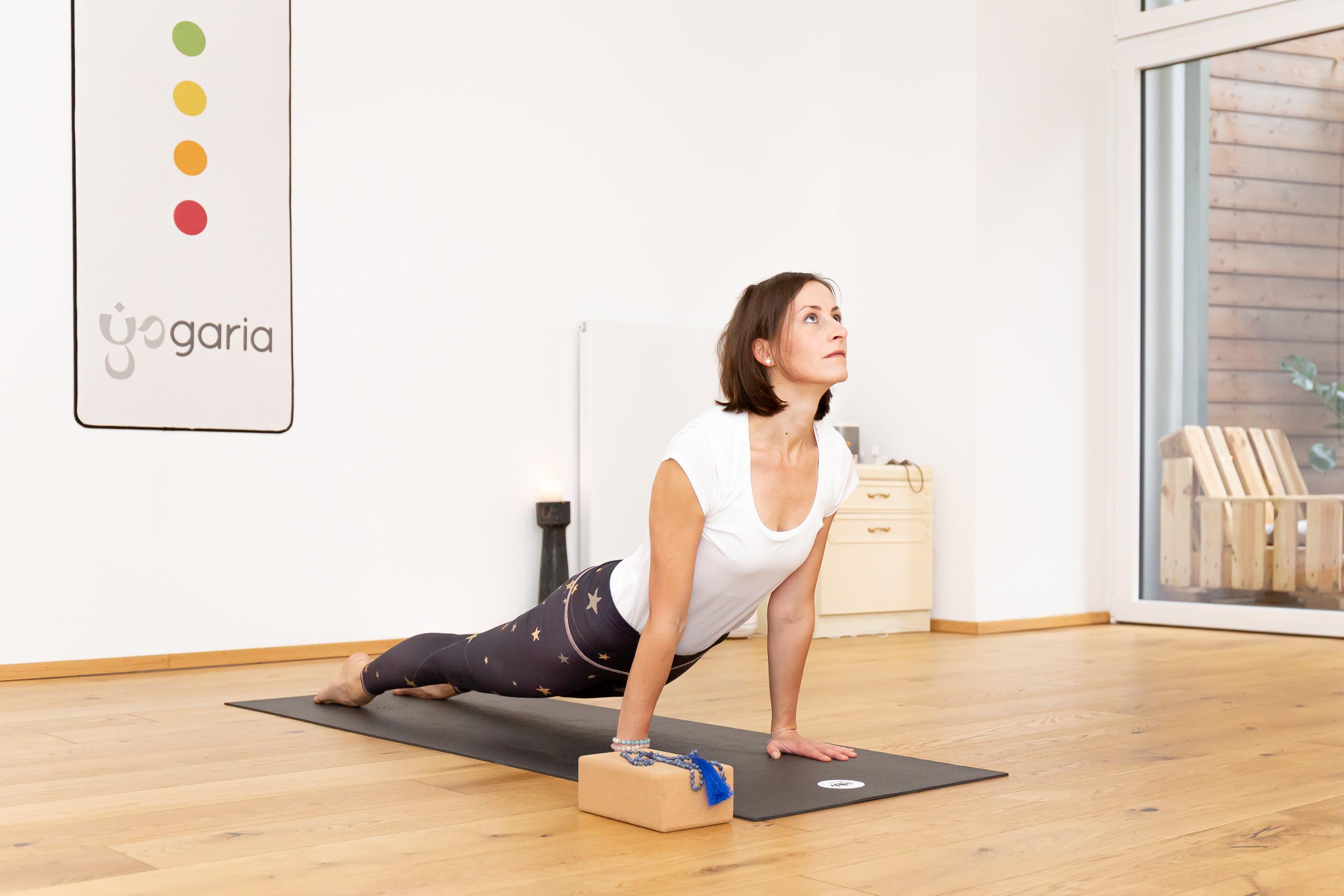 Klaudia in der Pose des aufschauenden Hundes auf der Yogamatte im Yogaraum der Yogaria, im Hintergrund das Logo der Yogaria und vor Klaudia liegt ein Yogablock mit ihrem Yogamala in blau darauf