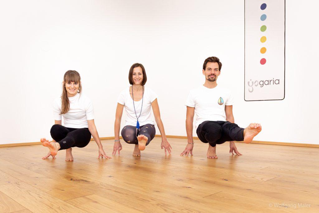 3 Yogis in einer Reihe, sie sitzen jeweils auf ihrer rechten Ferse und strecken ihr linkes Bein nach vorne aus.