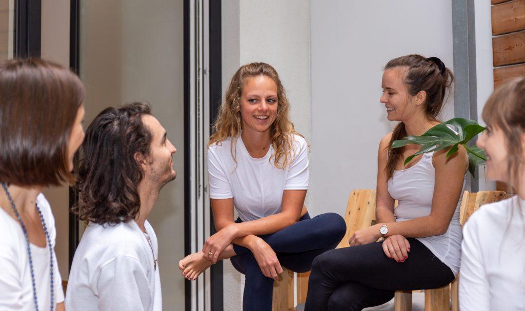 Das Yogaria Team sitzt im Kreis auf der Yogaria Terrasse und unterhält sich, Magdalena spricht offensichtlich und wird von allen anderen angesehen