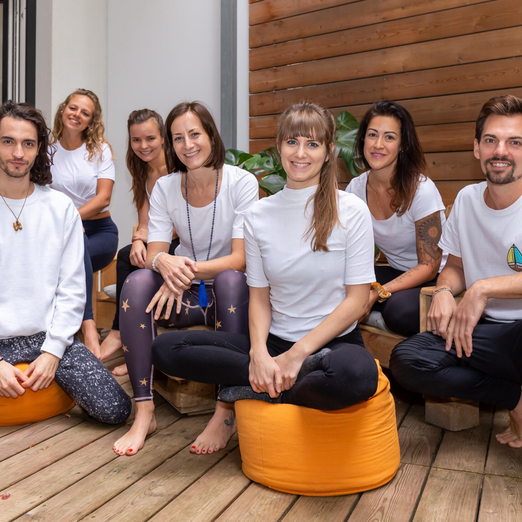 7 Yogalehrer*innen der Yogaria sitzen auf der Yogaria Terrasse