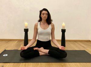 Angelina im Lotussitz auf der schwarzen Matte, im Hintergrund 2 schwarze Kerzenständer mit brennenden Kerzen, Angelina meditiert