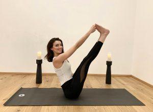 Angelina in einer Yogapose, sie sitzt seitlich auf der schwarzen Yogamatte und hat die Beine nach oben und vorne gestreckt, sie greift die großen Zehen mit Ihren Fingern und lächelt seitlich in die Kamera