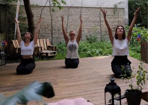 3 Yogis sitzen im Fersensitz auf dem Yogadeck im Garten der Yogaria, sie haben die Augen geschlossen und strecken ihre Arme zum Himmel, im Vordergrund sieht man eine Laterne, einen rosaroten Polster und ein paar Pflanzen ragen ins Bild, im Hintergrund ist der Garten der Yogaria zu sehen
