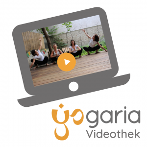 die Abbildung eines Laptops mit dem Bild am Bildschirm, darauf sind 4 Yogalehrerinnen in der Pose Malasana, die beiden in der Mitte haben die Hände gefaltet und die Ellbögen am Knie, die beiden äußeren Yogalehrerinnen haben die Arme jeweils zum Zentrum hin geöffnet, sie alle sind auf dem Yogadeck im Garten der Yogaria vor dem Baum