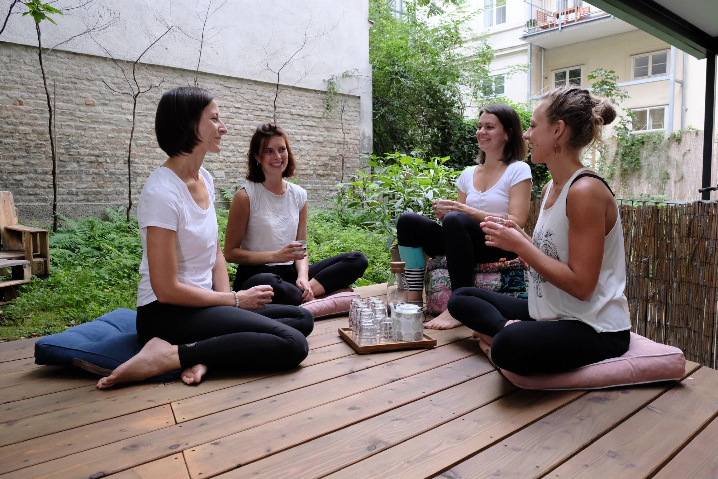4 Yogalehrerinnen sitzen im Kreis auf dem Yogadeck im Garten der Yogaria und unterhalten sich, sie trinken Tee und Wasser und sprechen miteinander