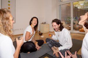 4 Yogalehrer/innen sitzen im Kreis im Yogaraum der Yogaria und trinken Tee, sie lachen herzlich