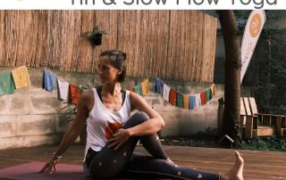Eine Yogalehrerin sitzt auf dem Yogadeck im Garten der Yogaria auf einer lila Yogamatte, sie sitzt in einer Twist-Position, hat das linke Bein gestreckt, das rechte Bein abgewinkelt und an den Oberkörper herangezogen, sie dreht sich über die rechte Seite und stützt sich mit der rechten Hand hinter ihrem Oberkörper ab und blickt über die rechte Schulter nach hinten, Sitzender Twist, Seated Twist