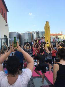 Unzählige Menschen beim Yoga im Freien, alle stehen in der Position des Baums und balancieren eine Bierflasche auf dem Kopf, im Hintergrund sieht man große Biertanks und gelbe Sonnenschirme