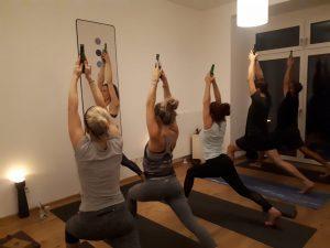 5 Personen im Yogastudio, von hinten, in der Position des High Lunge mit einer Bierflasche in den Händen nach oben gestreckt, auf schwarzen Yogamatten