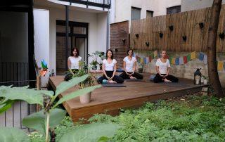 4 Yogalehrerinnen im Schneidersitz auf der Terrasse der Yogaria, sie haben die Augen geschlossen, die Hände im Schloss gefaltet und die Augen geschlossen, sie meditieren, im Vordergrund viel grün des Gartens