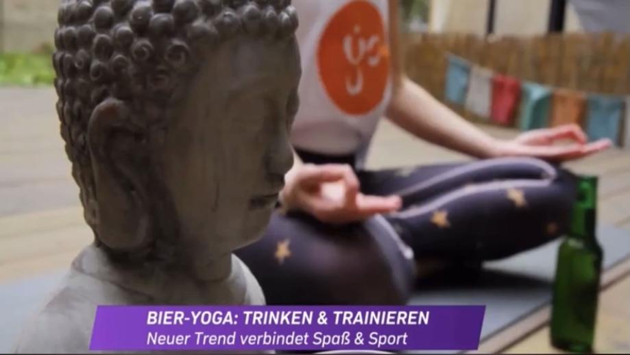 im Vordergund der Kopf einer kleinen Buddhastatue in der Yogaria, im Hintergrund Klaudia im Lotussitz, meditativ, mit einer Bierflasche vor ihr auf dem Boden
