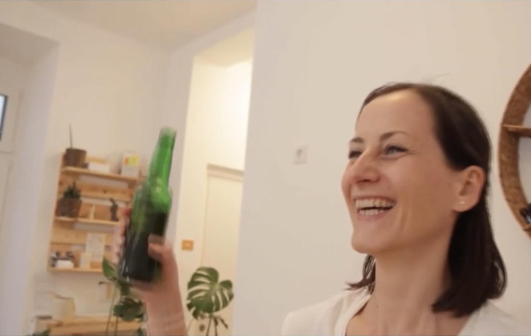Ein Porträtfoto von Klaudia, lächelnd mit einer kleinen grünen Bierflasche in ihrer rechten Hand