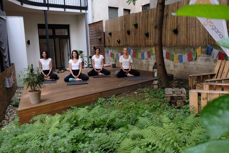 4 Mädls sitzen im Lotus Sitz auf dem Yogadeck im Yogaria Garten und meditieren