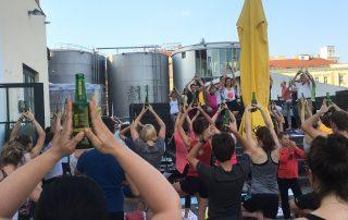 Eine Gruppe von Yogis aufgenommen von hinten, balancieren jeweils 1 kleine Bierfalsche am Kopf, in der Tree-Pose, also die Pose des Baumes, sie befinden sich auf dem Vorplatz der Ottakringer Brauerei in Wien