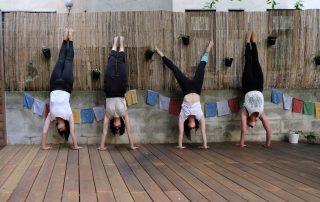 4 Yogalehrerinnnen in der Position des Handstandes vor dem Bambus Zaun und den Nepal Fähnchen im Garten der Yogaria