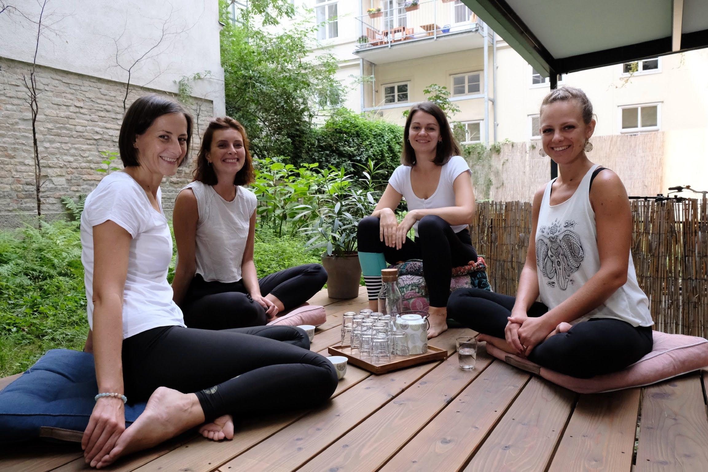 Klaudia, Elli, Katharina und Magdalena sitzen bei Tee und Wasser auf der Terrasse und lächeln in die Kamera