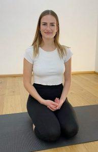Sophia im Heldensitz auf ihrer schwarzen Yogamatte in der Yogaria
