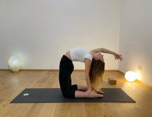 Sophia in der Haltung des Kamels mit einem Arm nach hinten gestreckt, in der Yogaria auf der schwarzen Yogamatte