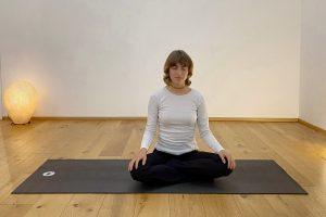 Bella meditierend auf der schwarzen Matte in der Yogaria, Sie sitzt im Schneidersitz und hat die Hände entspannt auf den Knien abgelegt
