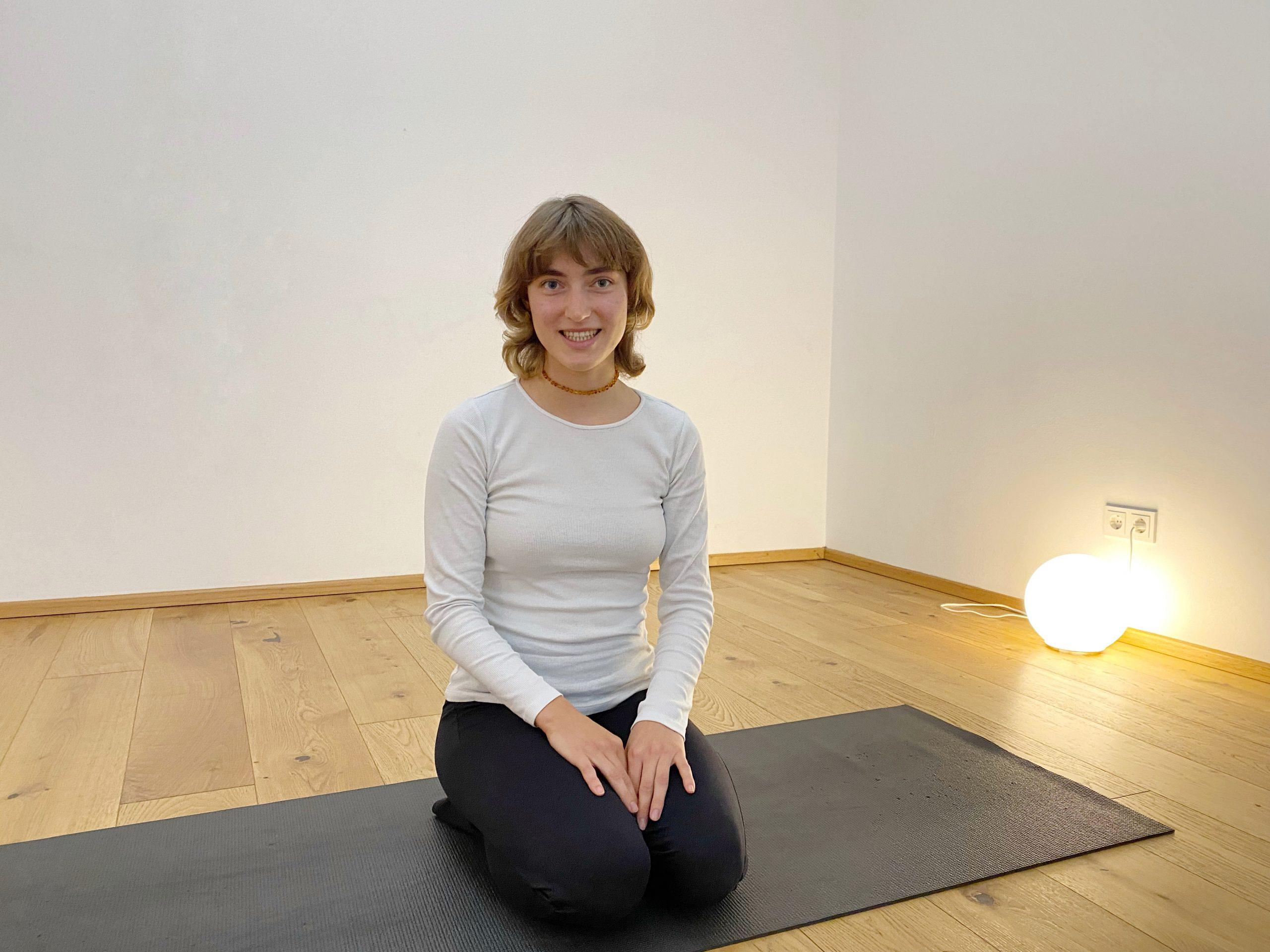 Bella Tröstl im Porträt, sitzend auf der schwarzen Yogamatte in der Yogaria, sie lächelt in die Kamera